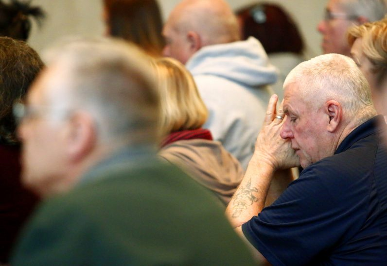 Marty Keller from Our Lady of Calvary Parish prays during the Mass for healing and recovery.
