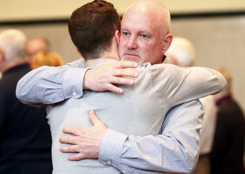 Ronald Meehan from St. Charles Parish in Sicklerville, N.J., embraces his son as a sign of peace. (Sarah Webb)