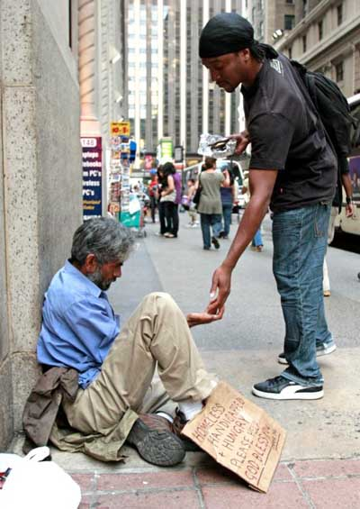 A passerby gives money to a homeless man sitting outside St. Francis of Assisi Church in New York City. Throughout Scripture, we find ample evidence of God calling us to give alms to the poor -- a reminder that almsgiving extends even beyond Lent. (CNS photo/Gregory A. Shemitz)