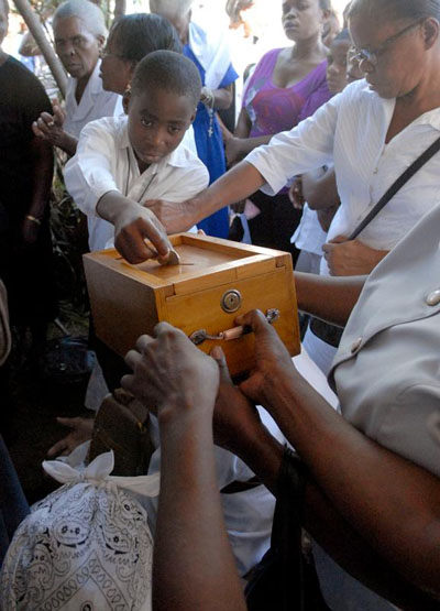 A Haitian boy drops money into the collection box during a Mass in Port-au-Prince. Almsgiving is a true Lenten sacrifice because we do it without expecting to receive anything in return. (CNS photo/Peter Finney, Clarion Herald)