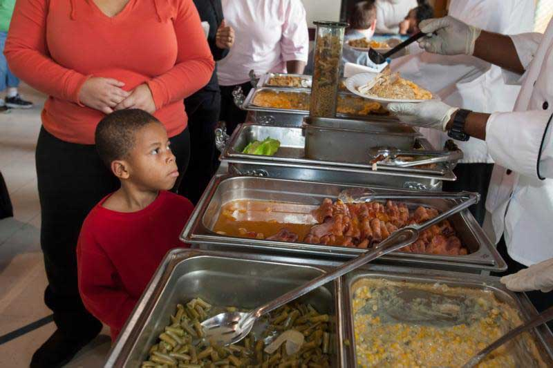 A boy looks on as meals are served to residents of a shelter for homeless women and children in Detroit. Almsgiving becomes a natural response to where prayer and fasting take us during Lent. (CNS photo/Jim West)