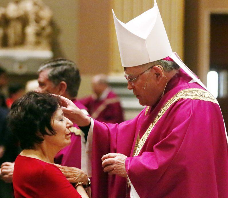 Archbishop Charles Chaput distributes ashes to Antonia Pugliese.