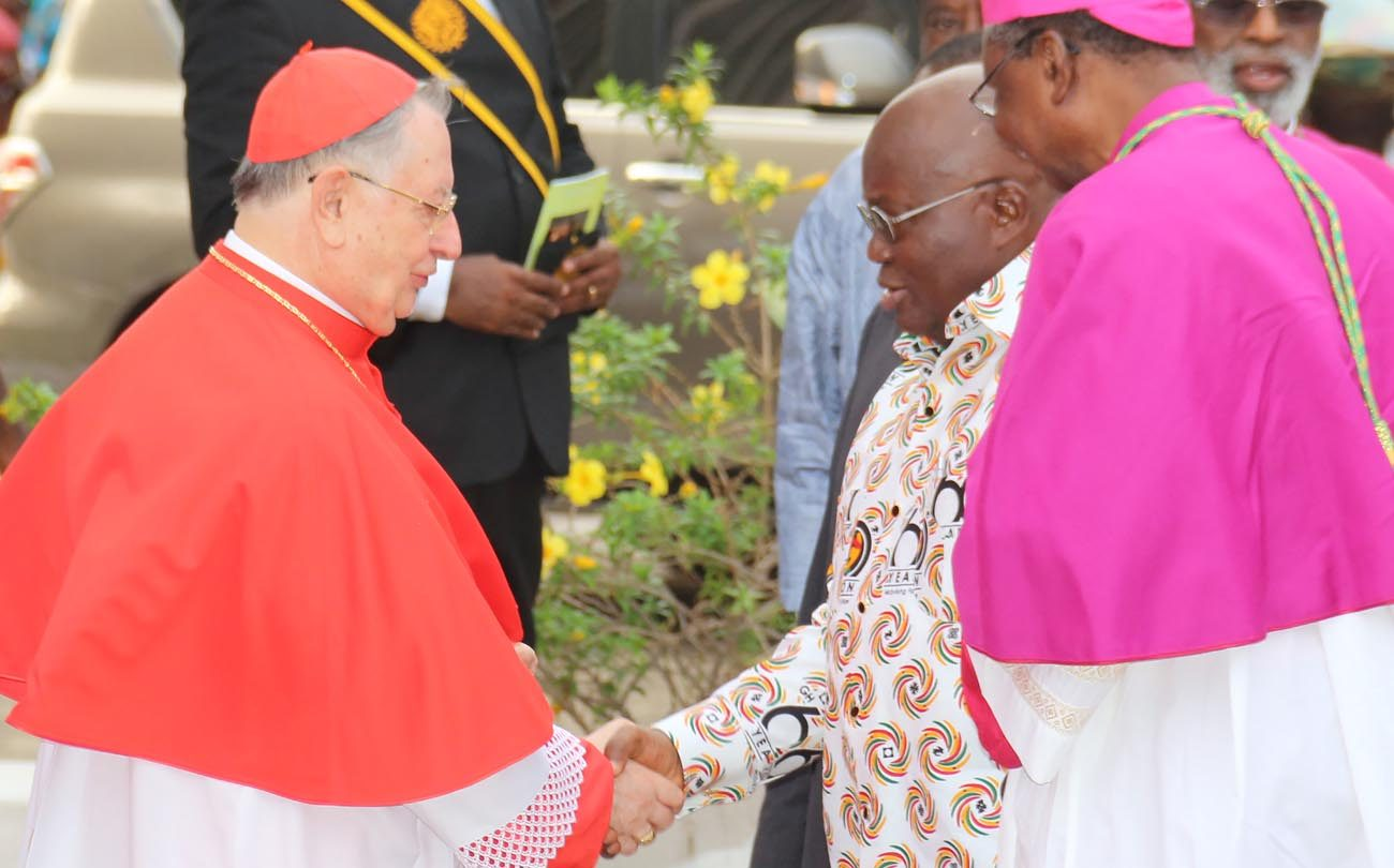 Cardinal Giuseppe Bertello, president of the commission governing Vatican City State, shakes hands with Ghanaian President Nana Addo Dankwa Akufo Addo during a March 4 ecumenical and interfaith prayer service at Holy Spirit Cathedral in Accra, Ghana. (CNS photo/Damian Avevor)