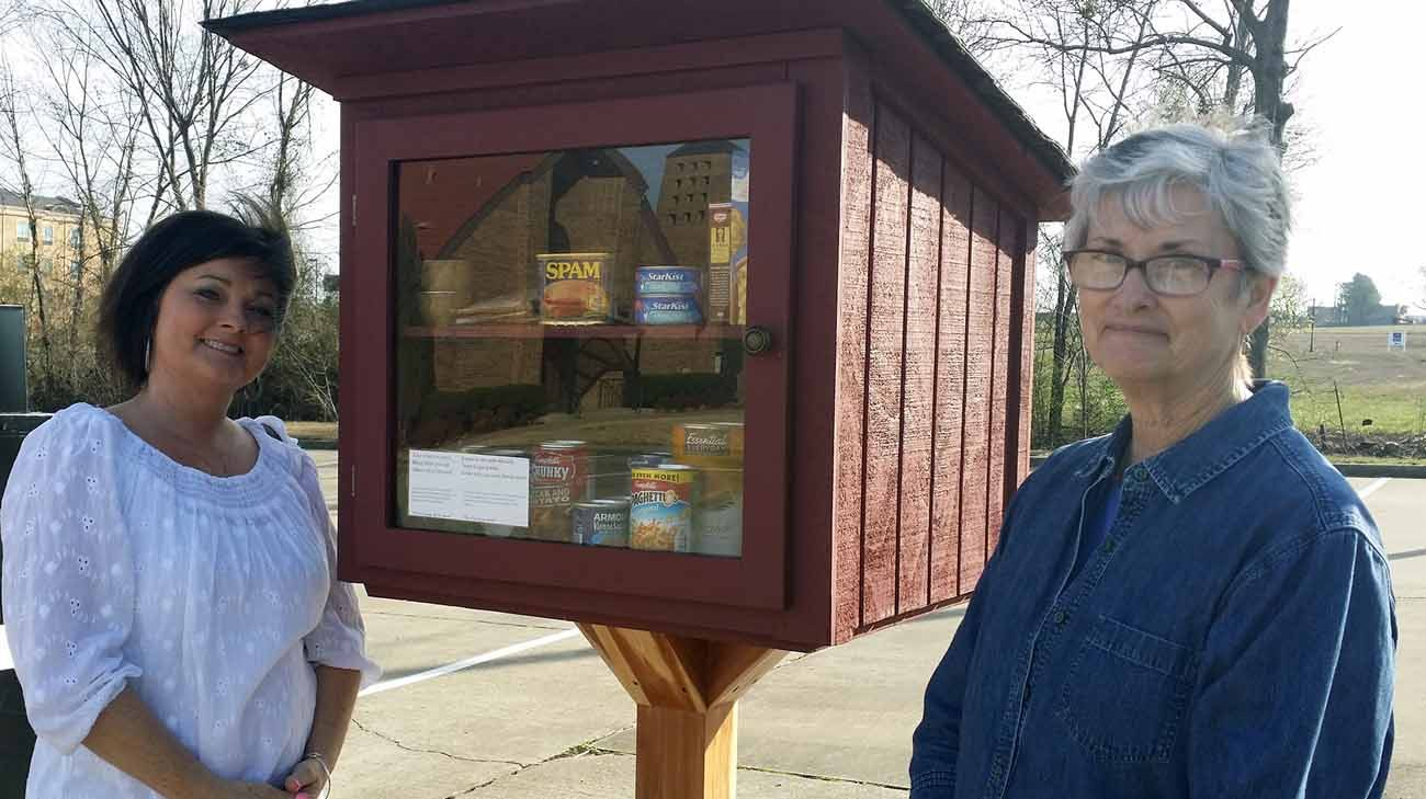 Betty Rose Neumeier and Annie Woody, members of St. Michael Church in Van Buren, Ark., pictured in a Feb. 23 photo, are two of the volunteers who stock the parish's blessing boxes. (CNS photo/Maryanne Meyerriecks, Arkansas Catholic)
