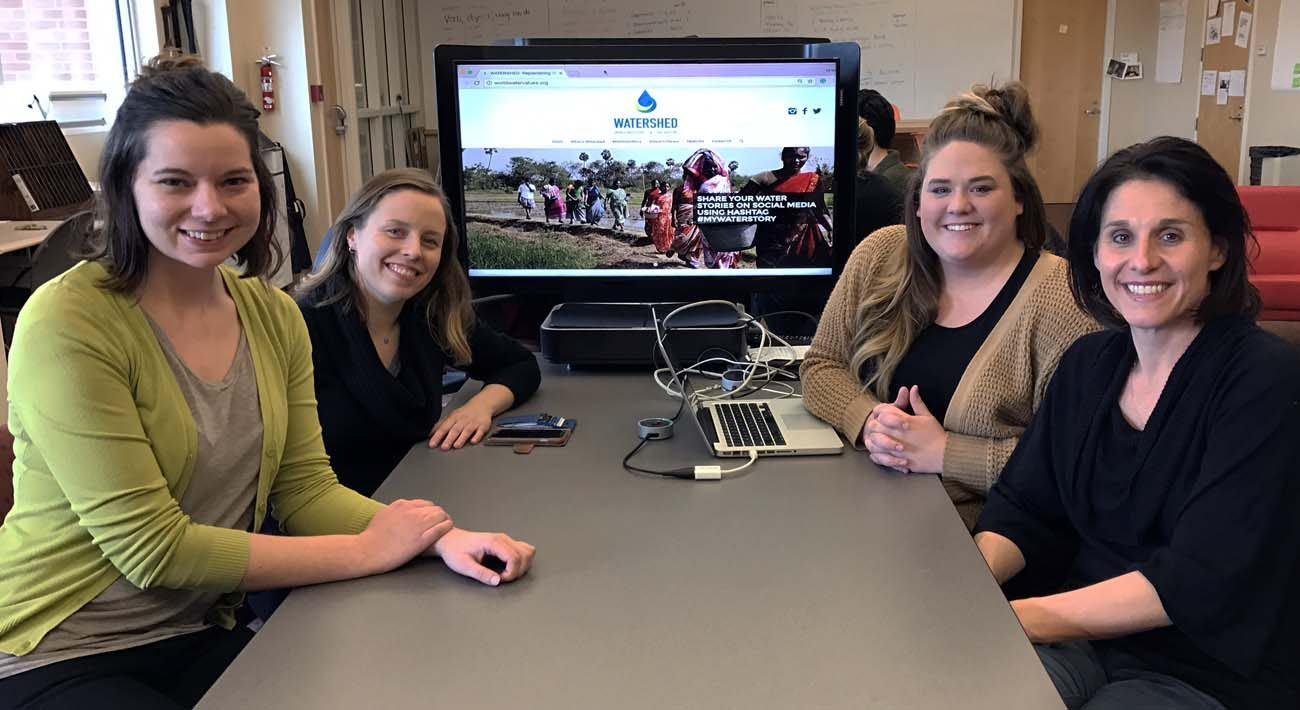 Faith Kellermeyer, Aiste Manfredini, Briee Eikenberry and Jennifer Palilonis, who are part of the team responsible for the Blue Roots project, show off their Blue Roots watershed website March 2 in Muncie, Ind. (CNS photo/Katie Breidenbach) .