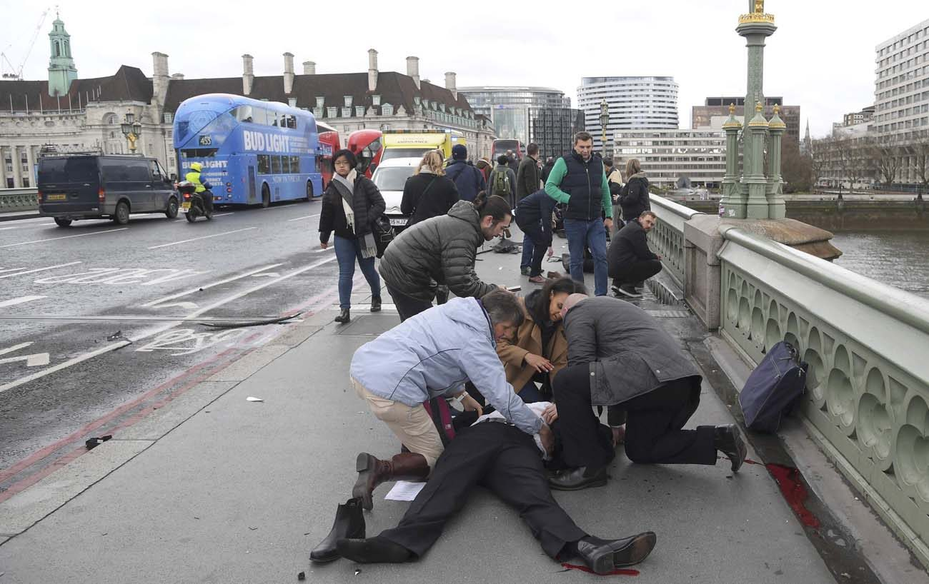 People assist an injured person after an attack on Westminster Bridge in London March 22. (CNS photo/Toby Melville, Reuters)