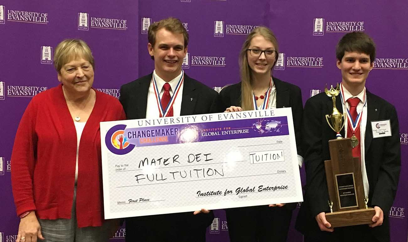Teacher Donna Lefler of Mater Dei High School in Evansville, Ind., stands with students Austin Bowen, Michaela Kunkler and Noah Harrison, who are holding a ceremonial check and trophy for their first-place finish in the University of Evansville's High School Changemaker Challenge in February. The three seniors won for designing a board game that focuses on bullying and the fight against it.  (CNS photo/courtesy Mater Dei High School)