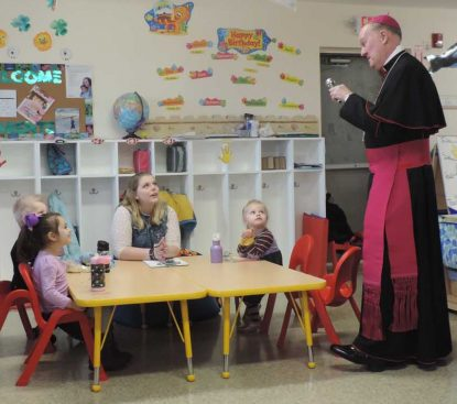 Bishop Michael Fitzgerald chats with a teacher and children at the dedication Precious Friends of St. Gianna Childcare Center, March 30.
