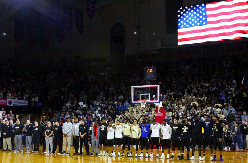 The Neumann-Goretti Saints stand with arms linked for the National Anthem.