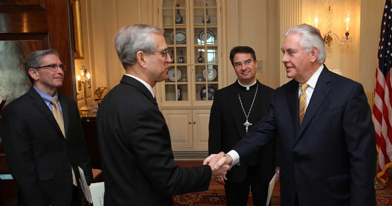 Bishop Oscar Cantu of Las Cruces, N.M., center, looks on as Stephen Colecchi, director of the Office of International Justice and Peace at the U.S. Conference of Catholic Bishops, is greeted by U.S. Secretary of State Rex Tillerson during a March 23 meeting at the  State Department in Washington. At far left is Stephen Hilbert, international policy adviser with the USCCB. (CNS photo/Bob Roller)