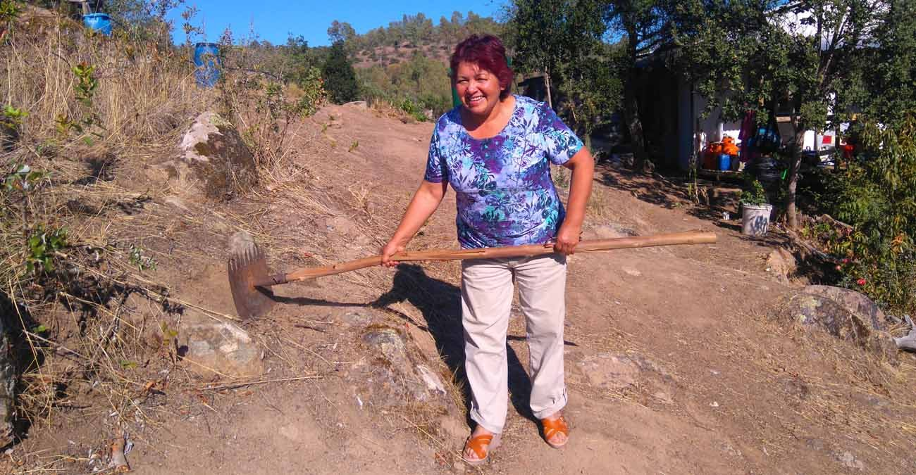 Ana Maria Araya Venegas from the Parish of Santa Rosa de Lavadero, Chile, displays the rake that helped save her house from recent forest fires in this March 13 photo. Prevention has helped parishes survive worst fires in Chile's history. (CNS photo/Jane Chambers)