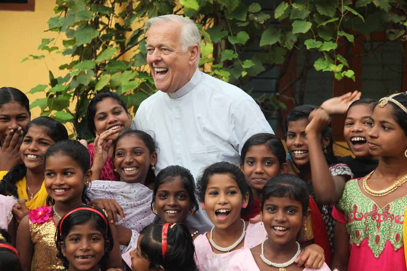 Msgr. John E. Kozar, secretary of the Catholic Near East Welfare Association, is pictured with young women in 2015 in Trivandrum, India. The agency is celebrating 90 years of service to Eastern Catholic churches and the poor in the Middle East, northeast Africa, India and Eastern Europe. (CNS photo/courtesy John E. Kozar, CNEWA)