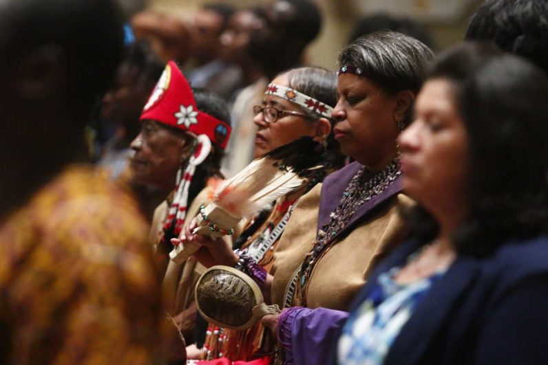 Members of the Native American community pray during mass.