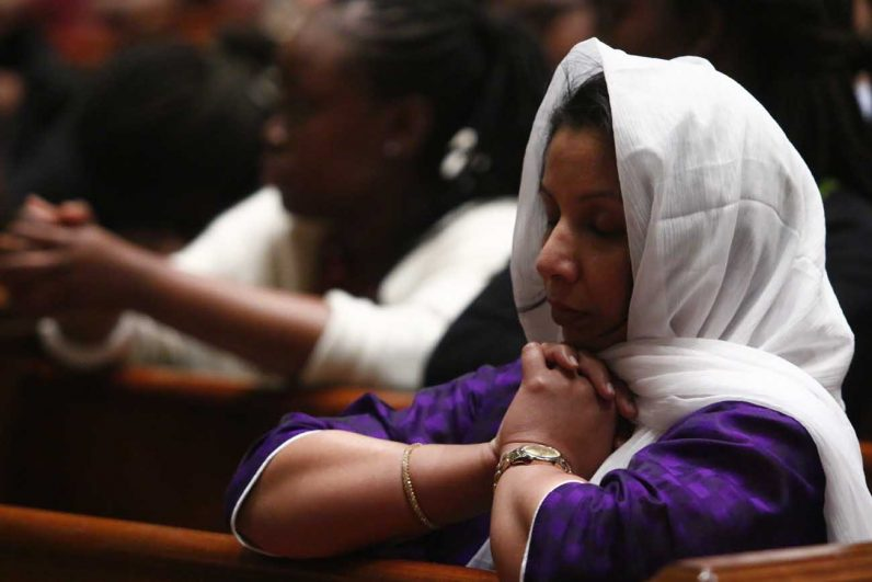 Preethy Mathew from the Indian Knanaya community prays during mass.