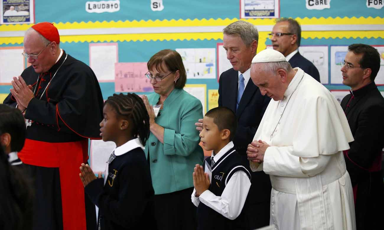 Cardinal Timothy M. Dolan of New York and Pope Francis pray with students in 2015 at Our Lady Queen of Angels School in the Harlem section of New York City. Cardinal Dolan March 9 urged President Donald Trump to follow through on a recent call for legislation that funds school choice for disadvantaged youth nationwide. (CNS photo/Tony Gentile, Reuters)