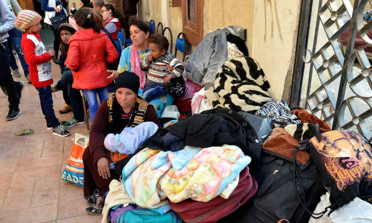 Displaced Egyptian Christian families, who used to live in the north of the Sinai Peninsula, sit near their belongings after arriving Feb. 24 at a church in Ismailia. Catholic churches in Ismailia, with help from Caritas, have helped Coptic Orthodox fleeing Islamic State attacks in North Sinai. (CNS photo/EPA)