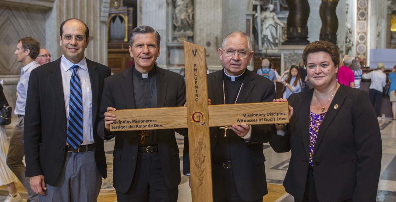Leaders in ministry to U.S. Hispanic Catholics stand in St. Peter's Basilica at the Vatican in 2016 with the Encuentro cross. They are from left: Alejandro Aguilera-Titus, national coordinator of the Fifth Encuentro; Archbishop Gustavo Garcia-Siller of San Antonio, chairman of the U.S. bishops' Committee on Cultural Diversity in the Church; Archbishop Jose H. Gomez of Los Angeles; and Mar Munoz-Visoso, executive director of the U.S. bishops' Secretariat of Cultural Diversity in the Church. (CNS photo/Robert Duncan)