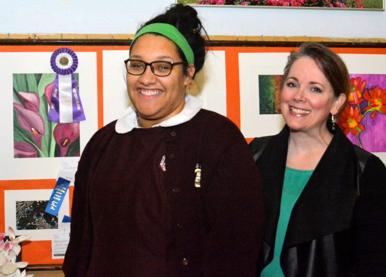 Little Flower senior Makayla Heyward receives a first-place award for her flower drawing. Makayla is shown with her art teacher Noreen Diehl.