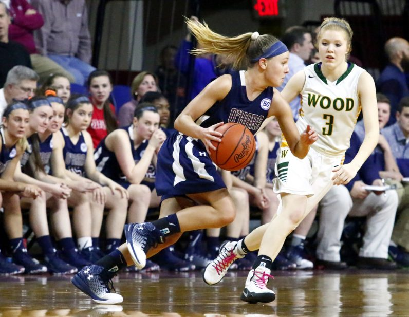 O'Hara's Mackenzie Gardler charges the basket with Wood's Shannon May guarding closely.
