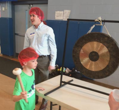 Jett Williamson rings a gong in the St. Monica Parish gym to signal that an additional 5,000 meals had been packaged. Looking on is Levi Keene of Catholic Young Adults of Chester County (CYACC).