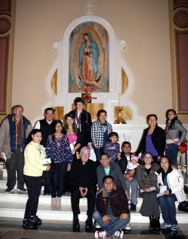 Father John Newns (front, center) poses with a group of his parishioners from St. Ann Parish, Phoenixville, by the shrine to Our Lady of Guadalupe at the Cathedral Basilica of SS. Peter and Paul. Many of the parishioners are new arrivals from Guatemala and Mexico.