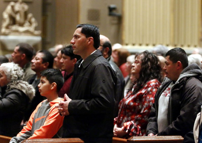 Juan Diaz and his son Karol from St. Rocco Parish, Avondale, pray at the prayer service for immigration. (Sarah Webb)