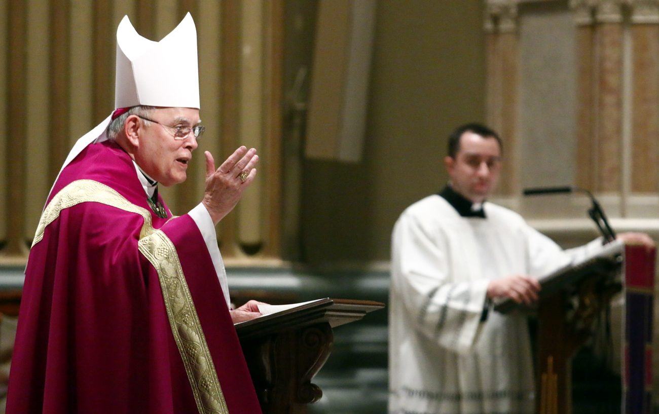 As Archbishop Charles Chaput preaches during the liturgy for immigrants and refugees March 19 at the Cathedral Basilica of SS. Peter and Paul, Father Thomas Viviano translates the homily for Spanish-speaking participants. (Sarah Webb)