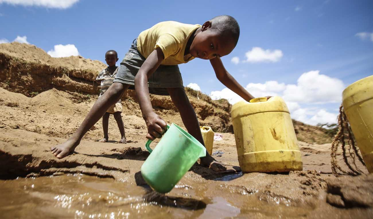 A boy collects water in a dry riverbed in Kitui, Kenya, in this 2015 file photo. (CNS photo/Dai Kurokawa, EPA)