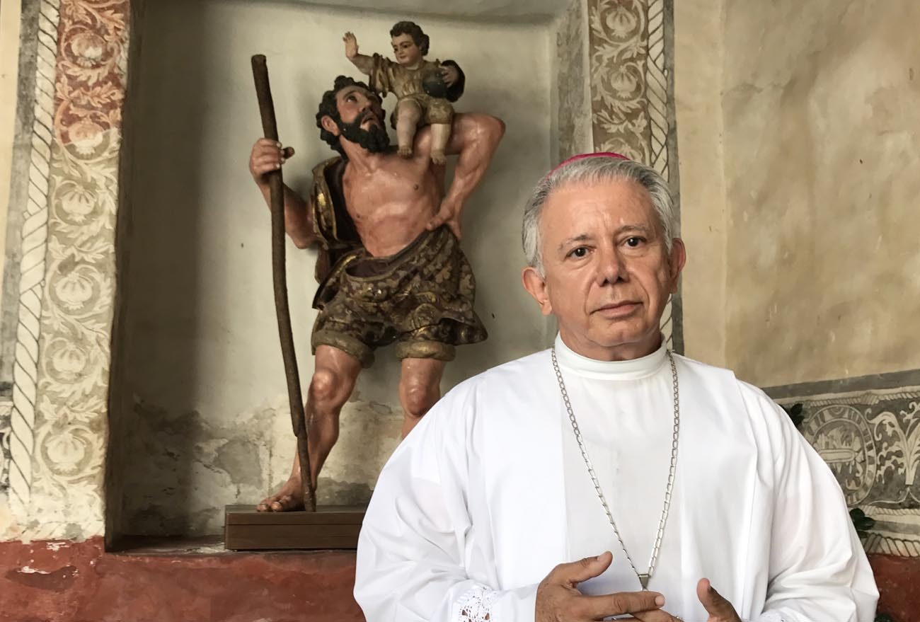 Bishop Ramon Castro Castro of Cuernavaca, Mexico, poses March 26 in the Assumption of Mary Cathedral in front of an image of St. Christopher from the colonial period. (CNS photo/David Agren)