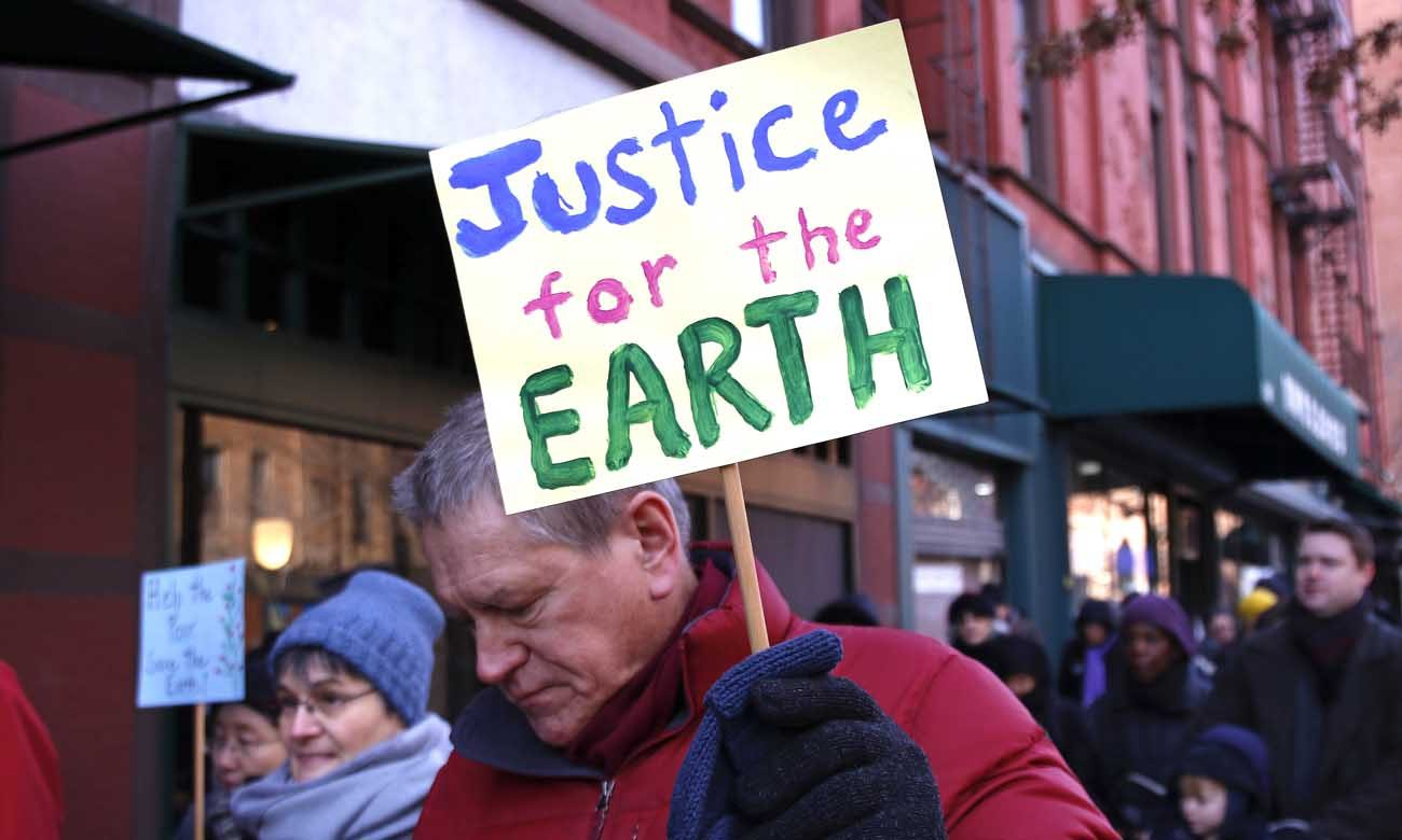 "A man carries a sign during the annual Martin Luther King Jr. Day Interfaith Peace Walk Jan. 18 in the Upper West Side neighborhood of New York City. The theme of this year's event was ""Hear the cry of the earth and the cry of the poor,"" from Pope Francis' encyclical ""Laudato Si'."" Seventeen Republicans in the House of Representatives are calling on their colleagues to express a commitment to ""conservative environmental stewardship."" (CNS photo/Gregory A. Shemitz)"