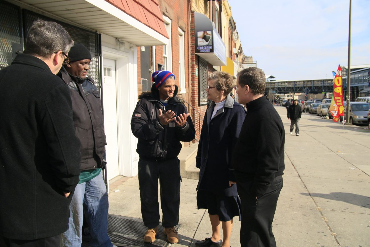 Residents of the Kensington section of Philadelphia talk with priests and a religious sister ministering at Mother of Mercy House, a Catholic outreach project in a neighborhood with many poor people including immigrants. (Sarah Webb)
