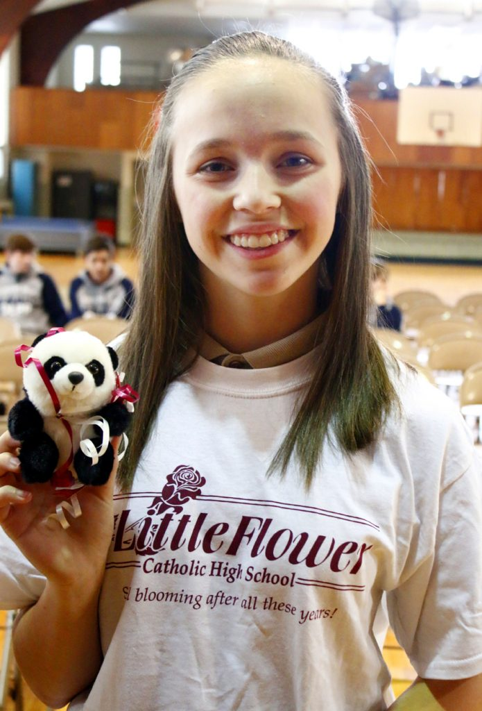 Alayna DeNight shows off the panda, the mascot of Little Flower High School, which she received with her T-shirt.