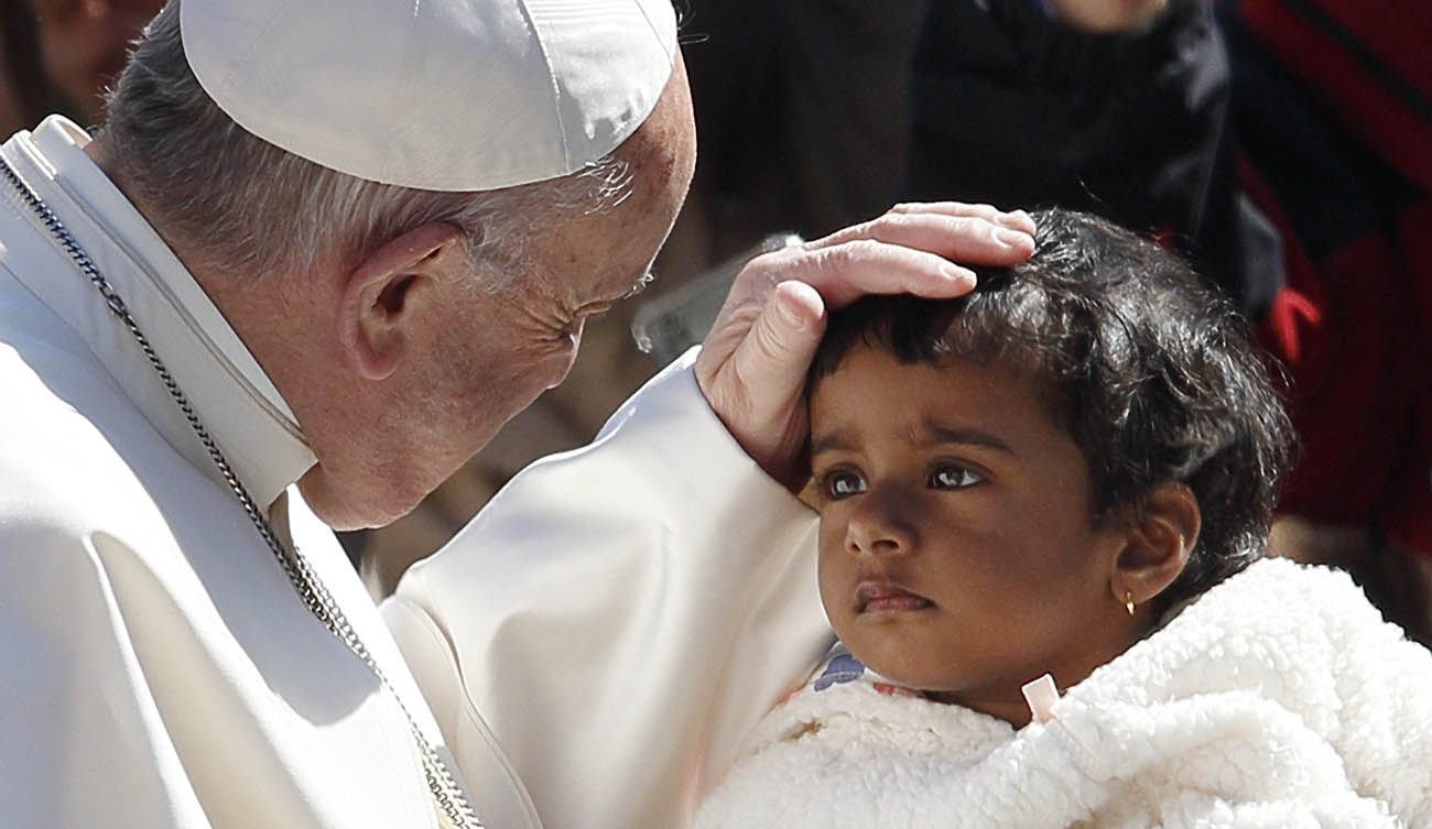 Pope Francis greets a child during his general audience in St. Peter's Square at the Vatican March 29. (CNS photo/Paul Haring)