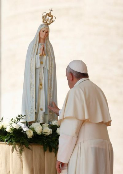 Pope Francis touches a statue of Our Lady of Fatima after praying in front of it during his general audience in 2015 in St. Peter's Square at the Vatican. Celebrating the 100th anniversary of apparitions of Our Lady of Fatima, Pope Francis will visit the Shrine of Our Lady of Fatima May 12-13. (CNS photo/Paul Haring)