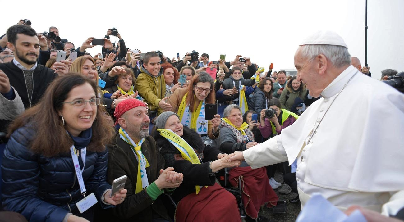 """Pope Francis greets people as he visits the """"White Houses,"""" a housing development for the poor, on the outskirts of Milan March 25. (CNS photo/L'Osservatore Romano)"""