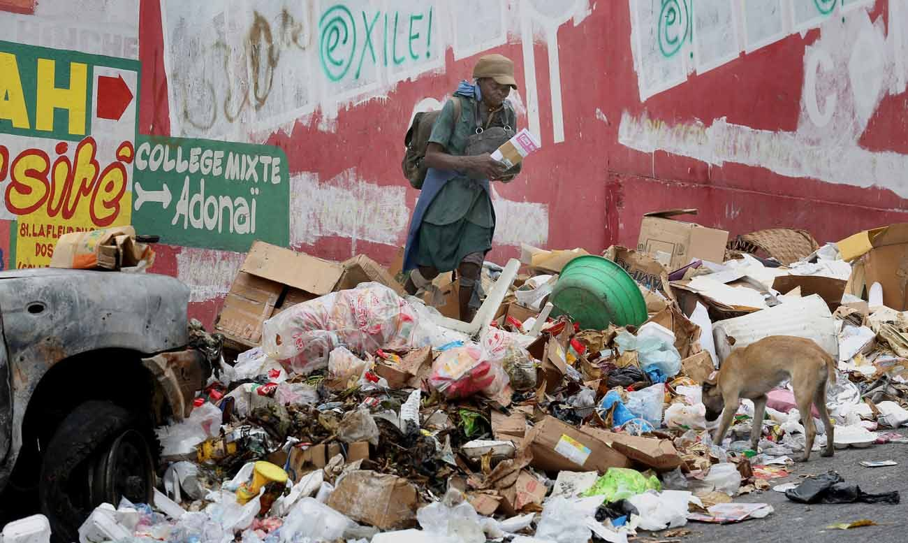"A woman and dog are seen amid garbage along a street in 2015 in Port-au-Prince, Haiti. Blessed Paul VI's 1967 encyclical ""Populorum Progressio"" rooted the Catholic Church in solidarity with the world's poorest nations. (CNS photo/Bob Roller)"