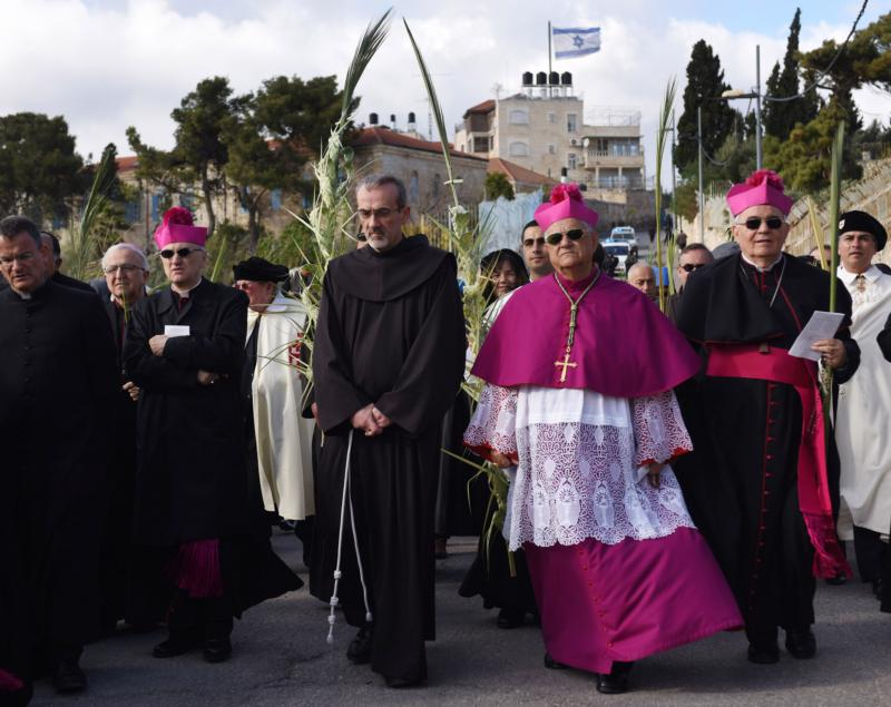 Now retired Latin Patriarch Fouad Twal of Jerusalem walks in the annual Palm Sunday procession on the Mount of Olives overlooking the Old City of Jerusalem March 20, 2016. The life and ministry of Jesus Christ was the fulfillment of centuries of prophecy, and when the Gospel was spread around the world, this point got great emphasis. (CNS photo/Debbie Hill)