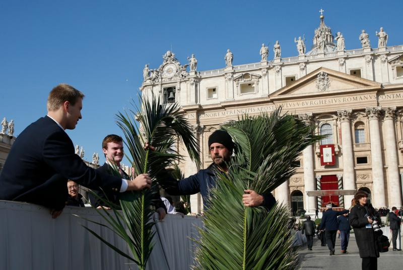 A worker hands out palm fronds before Pope Francis' celebration of Palm Sunday Mass in St. Peter's Square at the Vatican March 20, 2016. Palm Sunday produces an unsettling wave of emotions like no other day in the liturgical year -- from unbridled joy at the arrival of the Messiah in Jerusalem, to unfathomable sorrow at his crucifixion on a cross. (CNS photo/Paul Haring)