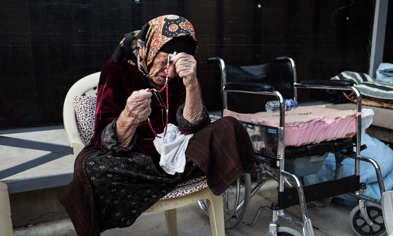 A displaced Iraqi woman prays the rosary in 2014 inside St. Joseph Church in Irbil, Iraq. The church gives refuge to thousands of people who were displaced by the Islamic State. (CNS photo/Daniel Etter, CRS)