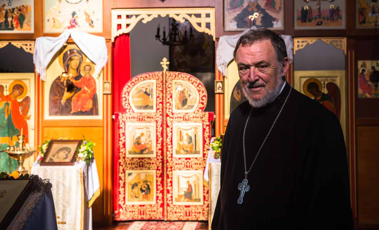 Father Lawrence Cross stands in front of the iconostasis in the Russian Catholic Church of St. Nicholas