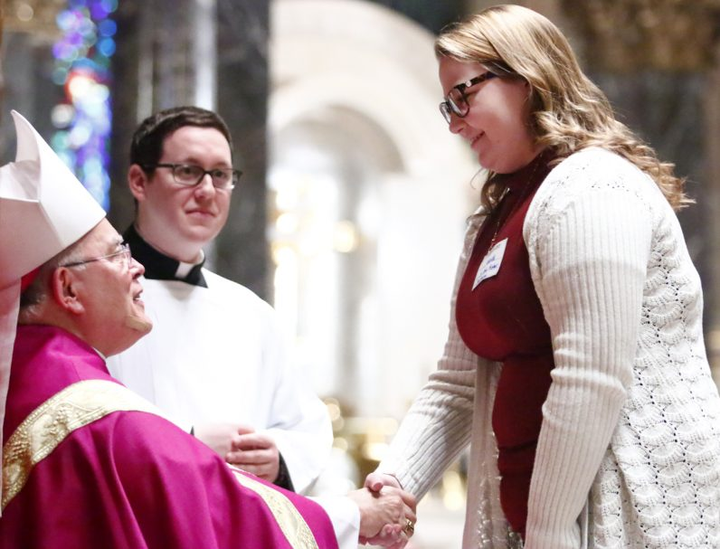 Catechumen Amanda from St. John Fisher in Boothwyn receives encouragement by Archbishop Charles Chaput.