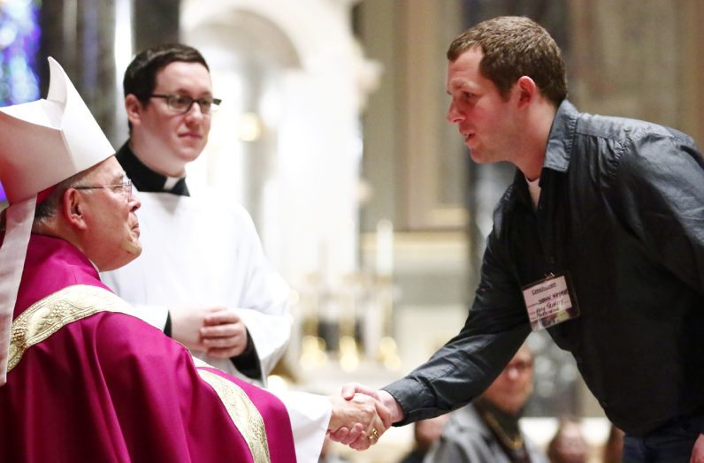 Shawn Weymer from Holy Trinity Parish in Morrisville is greeted by Archbishop Charles Chaput.