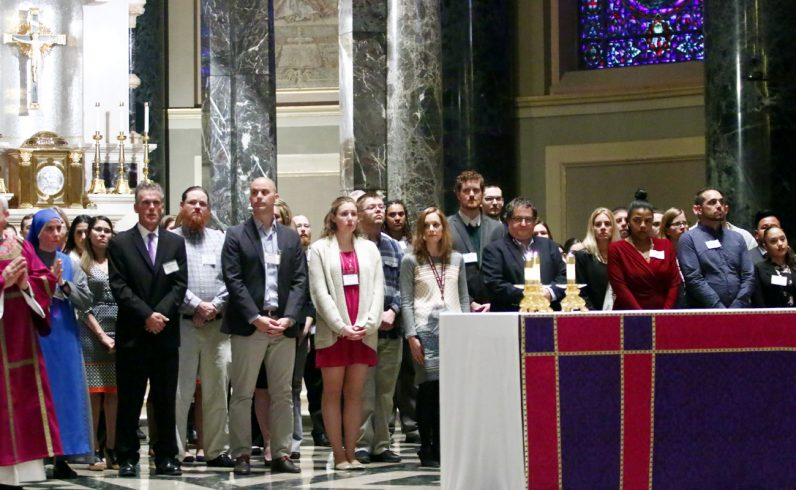 Catechumens stand before the altar as their baptismal sponsors state they are ready to be received by the church.