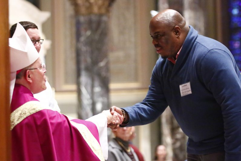 Candidate Kunle Folarin from St. John Chrysostom in Wallingford is greeted by Archbishop Chaput.