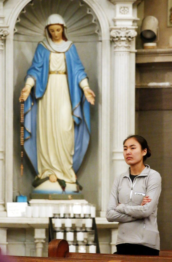Grace Yi listens to the Word of the Lord at St. Vincent de Paul Church on Saturday, March 25.
