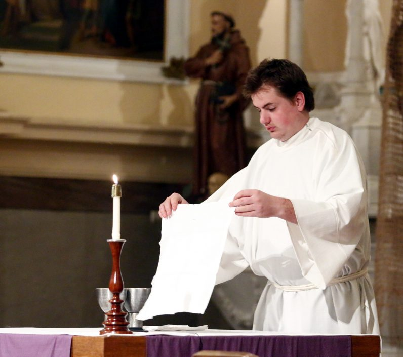 Edward Rigler prepares the altar for the Liturgy of the Eucharist.