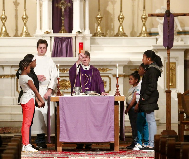 Vincentian Father Joseph Cummins elevates the Eucharist during Mass at St. Vincent de Paul Church in the Germantown section of Philadelphia.