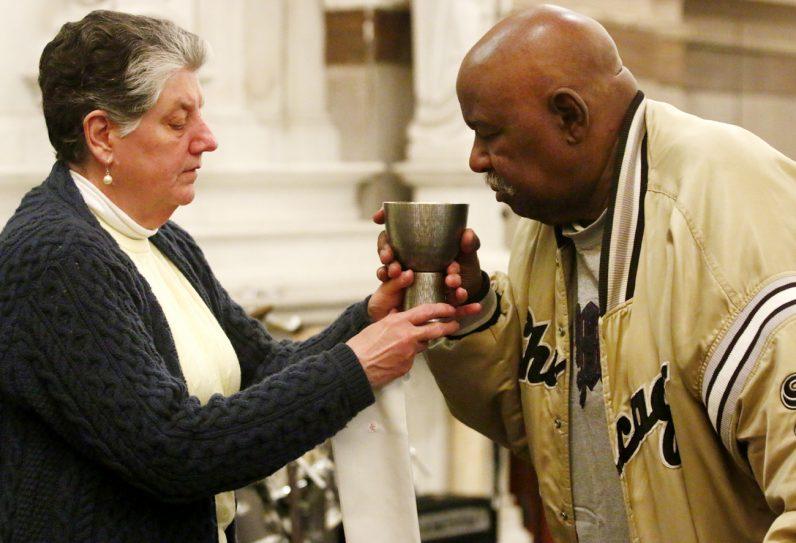 Jane Bonner distributes the Blood of Christ.
