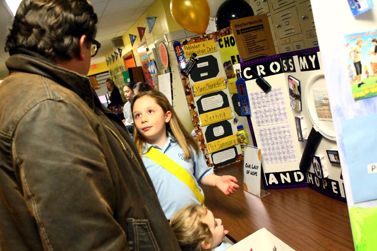Abigail Gillespie from Our Lady of Hope Regional Catholic School, Philadelphia, explains her project on a book she read for school. (Sarah Webb)