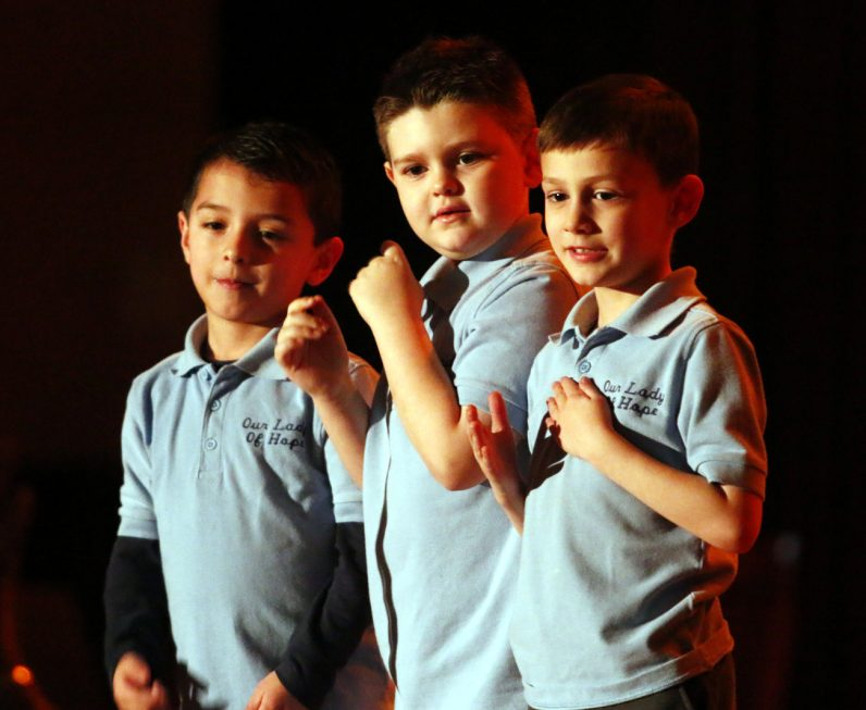 Kindergarten students (from left) Nicholas Cazabal, Robert Donahue and Christopher Shultz from Our Lady of Hope Regional School use sign language to perform a song during the Showcase of Excellence.